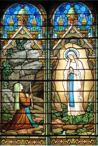 Vitrail au-dessus de l'entrée de l'église représentant les apparitions de Marie à Bernadette à Lourdes – paroisse de Saint Genis Laval
